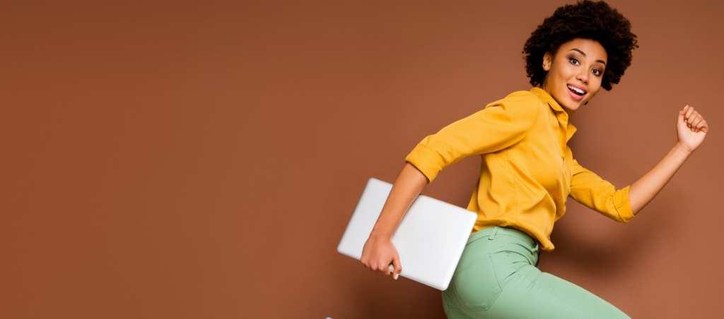 Femme afro souriante avec un ordinateur