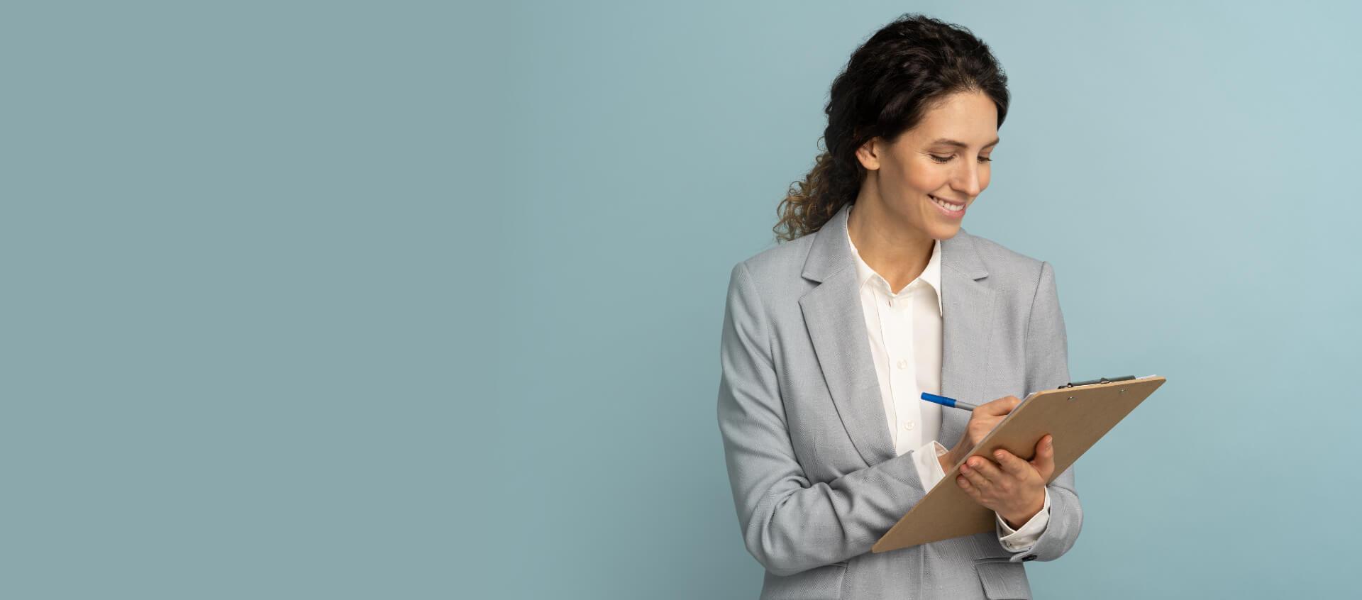 Femme en tailleur qui rédige dans un carnet