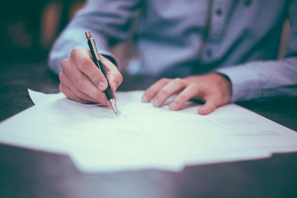 Business man qui écrit sur une feuille en papier